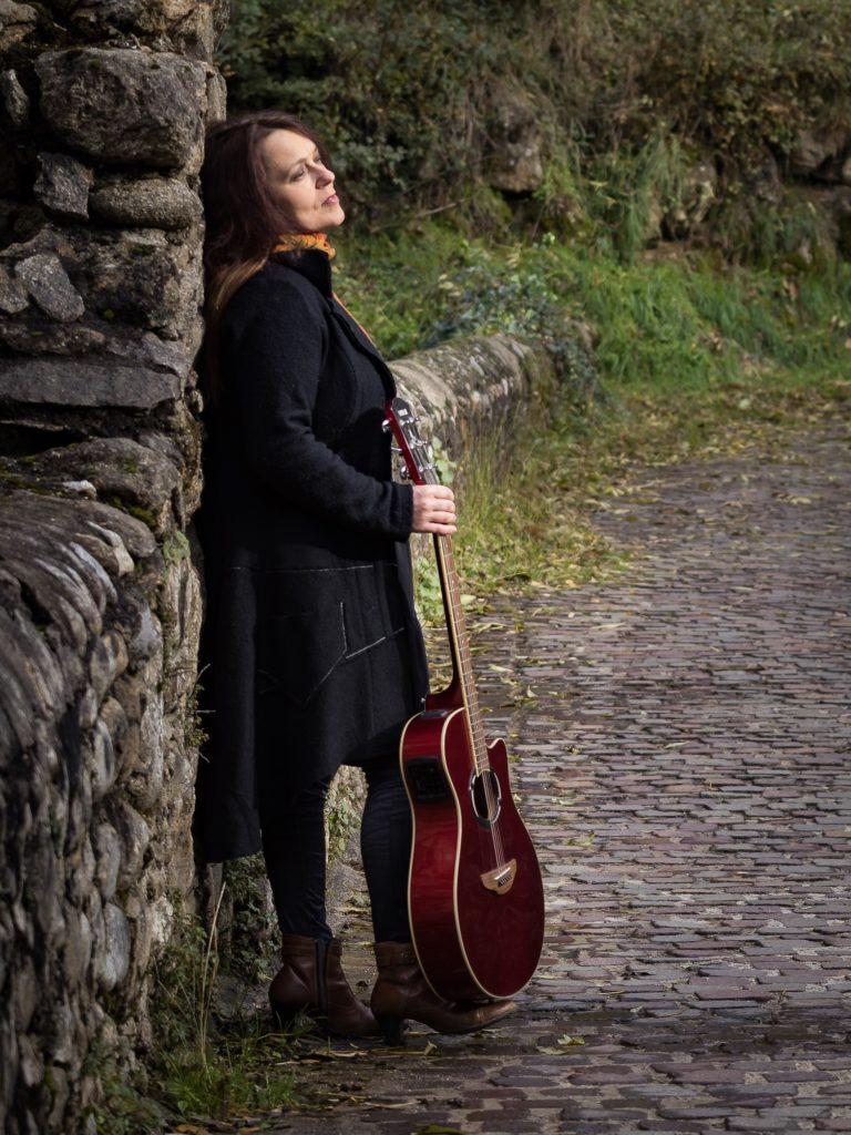 """Muriel Batbie Castell avec sa guitare au bord d'un chemin - photo illustrant l'album """"Par tous les chemins"""""""